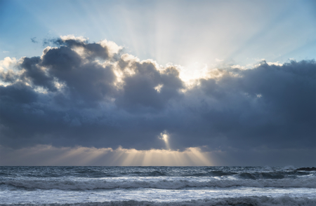 Beautiful cloud formations over sea at sunset with precuspular sun beams through clouds Stock Photo