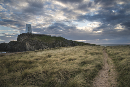Landscape image of Twr Mawr lighthouse with grassy footpath in foreground at  sunset Stock Photo