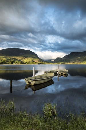 Beautiful moody stormy sky formations over stunning mountains lake landscape with rowing boats in foreground