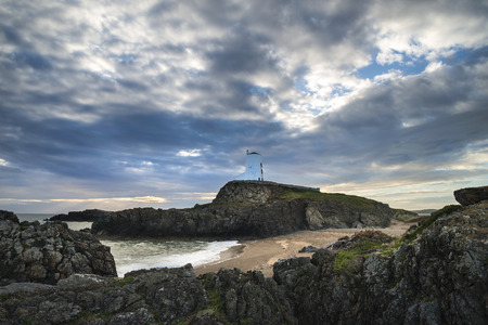 Twr Mawr lighthouse landscape from beach with dramatic sky and cloud formations