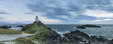 Beautiful Summer panorama landscape image of lighthouse on end of headland with beautiful sky
