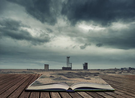 Cross processed conceptual post apocalyptic nuclear landscape with abandoned buildings concept coming out of pages in open book Stock Photo