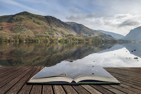 Beautiful Autumn Fall landscape image of Lake Buttermere in Lake District England concept coming out of pages in open book Archivio Fotografico