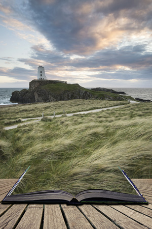Landscape image of Twr Mawr lighthouse with grassy footpath in foreground at  sunset concept coming out of pages in book Stock Photo