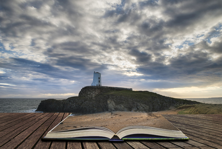 Twr Mawr lighthouse landscape from beach with dramatic sky and cloud formations concept coming out of pages in book Stock Photo