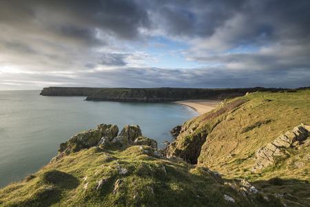 Beautiful sunrise landscape image of Barafundle Bay on Pembrokeshire Coast in Wales
