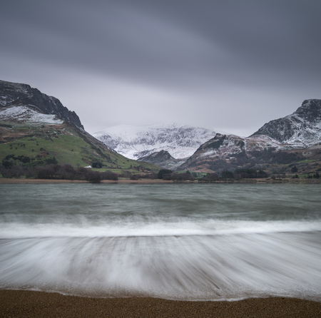 Beautiful sunrise landscape image in Winter of Llyn Nantlle in Snowdonia National Park with snow capped mountains in background