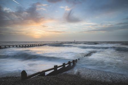 Beautiful moody stormy landscape image of waves crashing onto beach at sunrise Foto de archivo