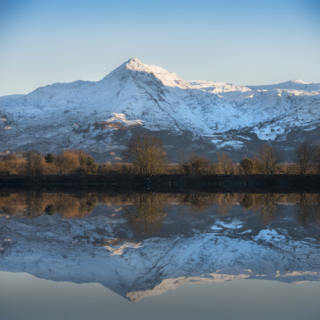Beautiful Winter landscape image of Mount Snowdon and other peaks in Snowdonia National Park