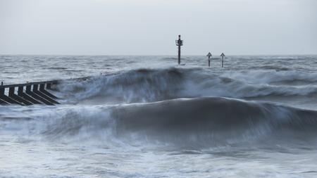 Beautiful moody stormy landscape image of waves crashing onto beach at sunrise Stock Photo