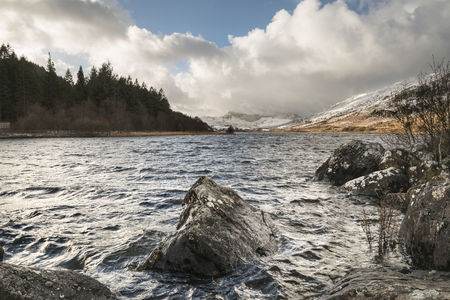Beautiful sunrise landscape image in Winter of Llynnau Mymbyr in Snowdonia National Park with snow capped mountains in background Stock Photo