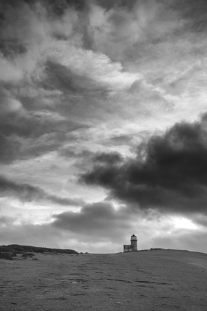 Beautiful black and white landscape image of Belle Tout lighthouse on South Downs National Park during stormy sky