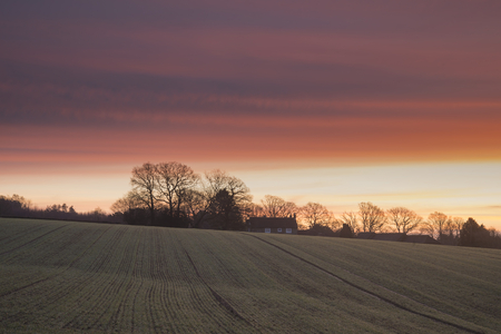 Stunning Winter sunrise over farmhouse in English countryside landscape