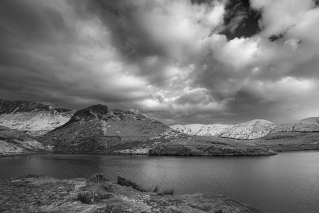 Beautiful  black and white Winter landscape image of Llyn y Dywarchen in Snowdonia National Park