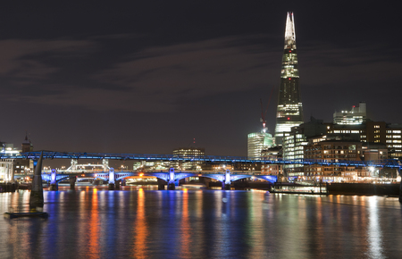 Landscape image of the London skyline at night looking along the River Thames