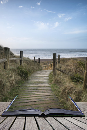 Sunrise landscape image of sand dunes system over beach with wooden boardwalk in pages of book Stock Photo - 97397948