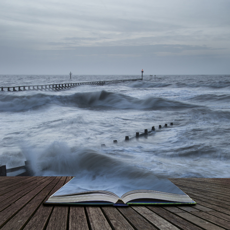 Beautiful moody stormy landscape image of waves crashing onto beach at sunrise in pages of book