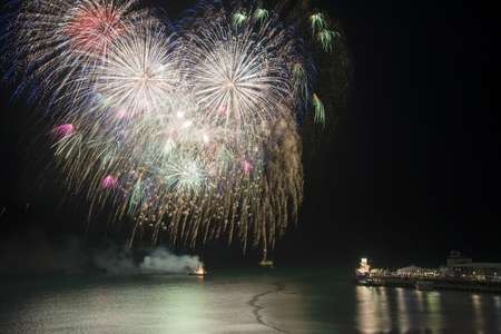 Fireworks display over sea with pier  and boats in water landscape scene