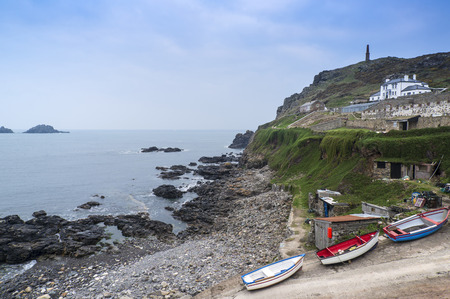 Buildings and boats on the Cape Cornwall headland landscape in Cornwall England Stock Photo
