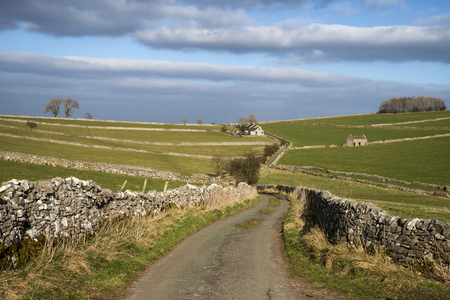 Road leading to farm house in Peak District landscape on stromy Summer day