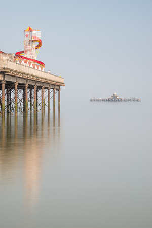 Minimalist fine art image of colorful pier in juxtaposition with old derelict pier in background