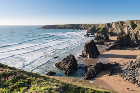 Beautiful dusk sunset landscape image of Bedruthan Steps rock stacks on West Cornwall coast in England