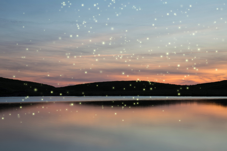 Beautiful Summer sunset landscape of fireflies glowing above vibrant lake and hills in distance