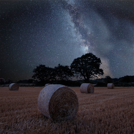 Stunning vibrant Milky Way composite image over landscape of field of hay bales in countryside