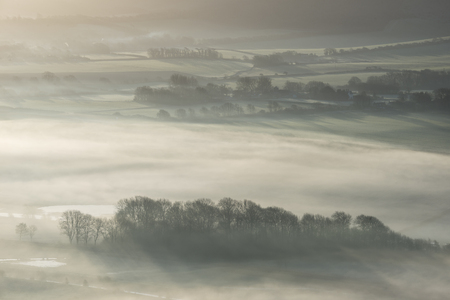 Beautiful foggy English countryside landscape at sunrise in Winter with layers rolling through the fields Banco de Imagens