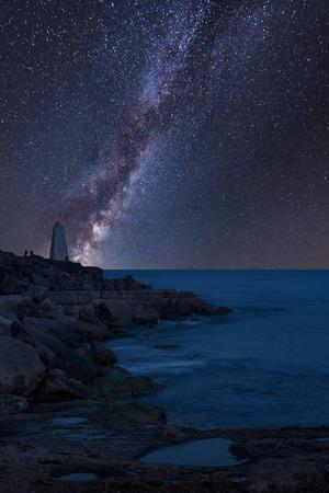 Stunning vibrant Milky Way composite image over landscape of Rocky cliff landscape over ocean