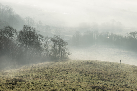 Beautiful foggy English countryside landscape at sunrise in Winter with layers rolling through the fields Stock Photo