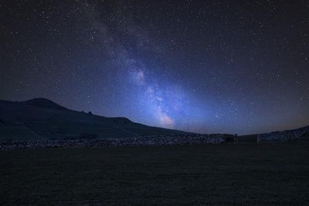 Stunning vibrant Milky Way composite image over landscape of Peak District landscape National Park in England