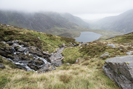 Moody landscape image of Llyn Idwal in Glyders mountain range in Snowdonia during heavy rainfall in Autumn