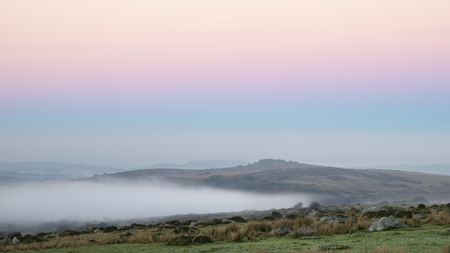 Stunning foggy sunrise landscape over the tors in Dartmoor revealing peaks through the mist