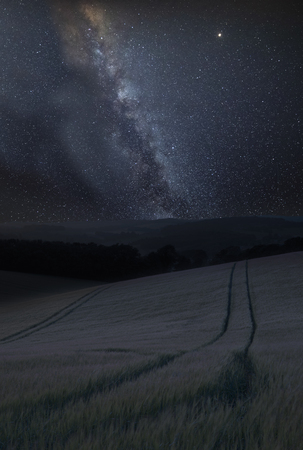 Stunning vibrant Milky Way composite image over landscape of Summer field of wheat