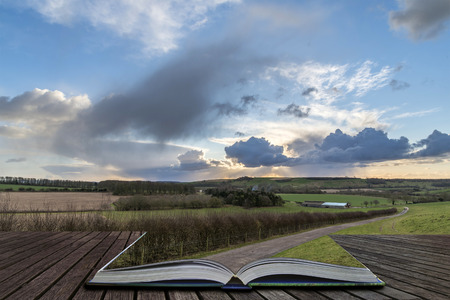 Beautiful stormy dramatic cloud formations over English countryside landscape coming out of pages of open story book