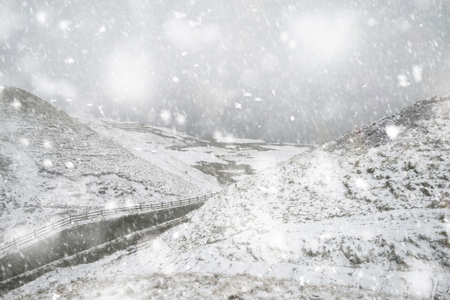 Stunning Winter landscape image around Mam Tor countryside in Peak District England in heavy snow storm