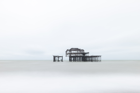 Landscape image of derelict Victorian West Pier at Brighton in West Sussex with moody evening sky 免版税图像