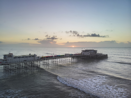 Drone aerial view landscape image of Worthing pier on Sussex coast in England at sunrise 写真素材