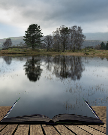 Beautiful landscape image of moody storm clouds over Kelly Hall Tarn in Lake District during late Autumn Fall afternoon coming out of pages of open story book