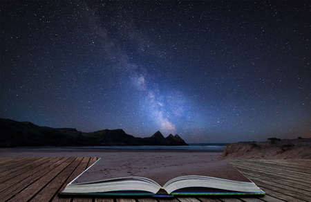 Stunning vibrant Milky Way composite image over landscape of yellow sandy beach Three Cliffs bay coming out of pages in magical story book Archivio Fotografico