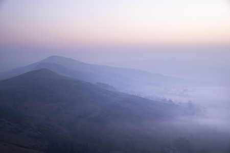 Beautiful Winter sunrise landscape image of The Great Ridge in the Peak District in England with mist hanging around the peaks