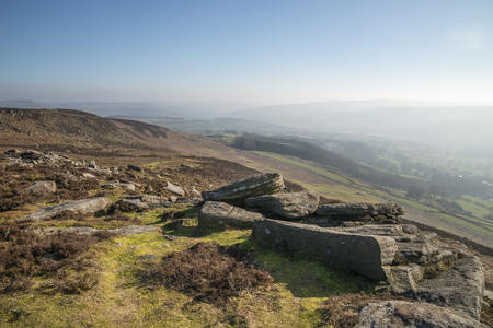 Beautiful landscape image of the Peak District in England viewed from Bamford Edge with Lose Hill and Mam Tor visible through the distant haze of a Winter day