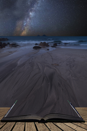 Stunning vibrant Milky Way composite image over landscape of Beautiful beach  coming out of pages in magical story book