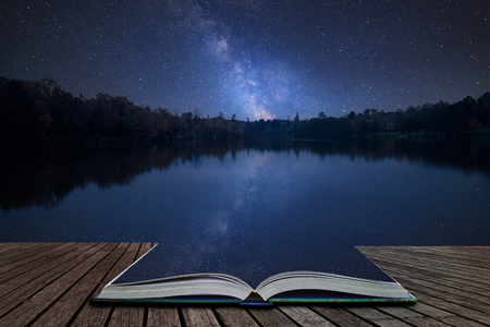 Stunning vibrant Milky Way composite image over landscape of still lake coming out of pages in magical story book 版權商用圖片