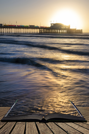 Beautiful sunrise landscape image of Worthing pier in West Sussex during Winter in pages of open book, story telling concept