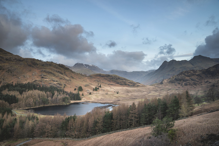 Stunning sunrise landscape image of Blea Tarn in UK Lake District with Langdales Range in background