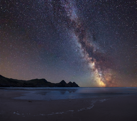 Stunning vibrant Milky Way composite image over landscape of yellow sandy beach Three Cliffs bay