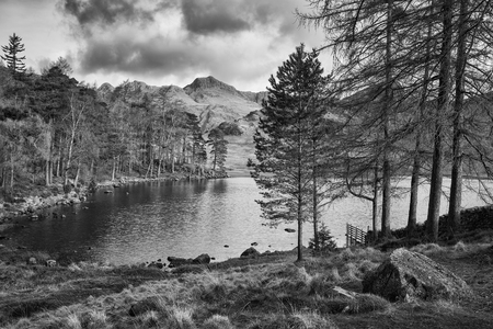 Stunning sunrise landscape image of Blea Tarn in UK Lake District with Langdales Range in background in black and white
