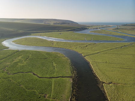 Beautiful aerial drone landscape image of meandering river through marshland at sunrise